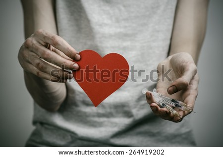 The fight against drugs and drug addiction topic: skinny dirty addict holding a syringe with a drug and red heart on a dark background