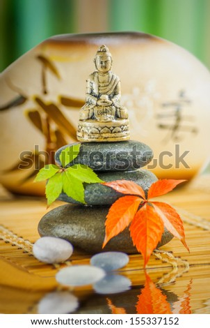 The figure of Buddha on a Zen stones with red and green leaves at the bamboo mat, reflected in water