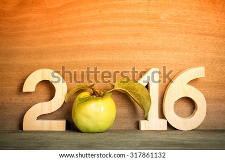 The figures in 2016 with an apple instead of the number 0 on the gray wooden background. Toned. - stock photo