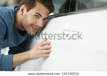 The final check. Handsome young men examining a car at the dealership - stock photo
