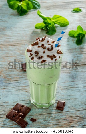 The final step of the milkshake recipe. Served drink with chocolate chips, whipped topping, kiwi and blue straw. Leaves of mint in the background. - stock photo
