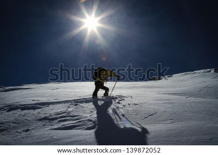 The final summit push on skis to the mountain summit under the low winter sun in the alps.  Kicking in a new skin track in the fresh blowing snow.