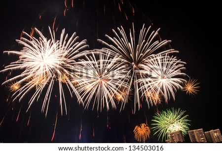 The fireworks display in black sky background to celebrate the New Year of 2013 at Pattaya city, Thailand. - stock photo