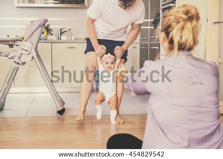the first baby steps. a happy family indoor. daily family life - stock photo
