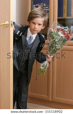 The first-grader with a bouquet enters into a class