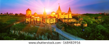 The first rays of the sun fall on the ancient walls of the fortress in the town of Kamenetz-Podolsk.  the ancient fortifications, amid its beauty bridge to the bastions, walls, towers, domes beautiful - stock photo