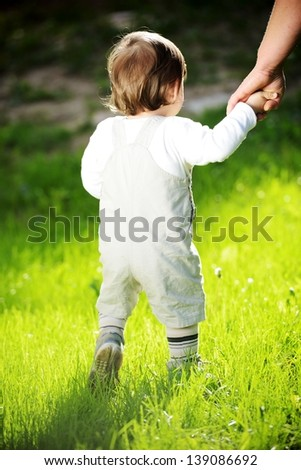 The first steps of the baby kid - stock photo