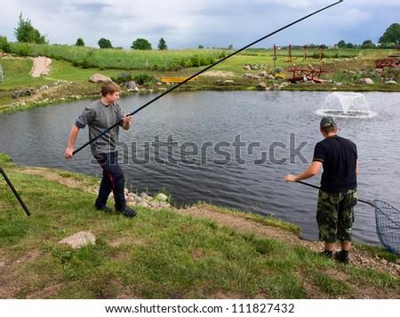 The fisherman at the lake on green coast - stock photo