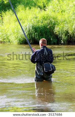 The fisherman fishes in the river - stock photo