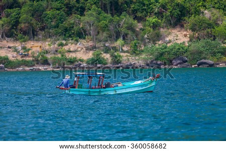 the fisherman floats in a boat on the sea - stock photo