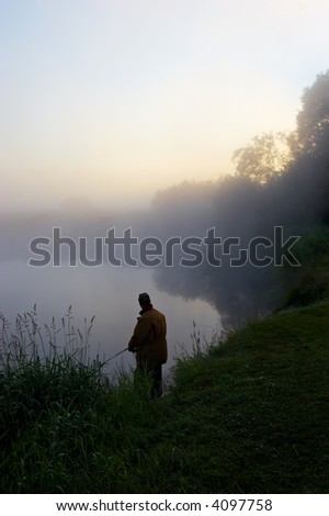 The fisherman in the early, foggy morning on the river