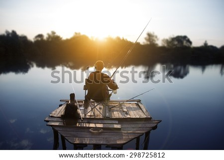 the fisherman is fishing on a lake in the early morning. - stock photo