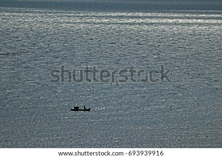 The fishing boat on the sea in sunset