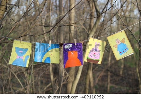 The five drawn card with a picture of a pink Easter bunny, two cats, yellow elephant and angel clothespins attached to a rope in autumn forest