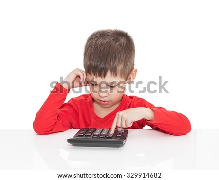 The five-year boy sitting at a white table and presses the button calculator isolated on white - stock photo