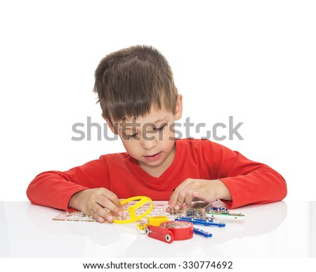 The five-year-old boy sits at a white table and plays an electronic designer (meccano, constructor),  isolated on a white background  - stock photo