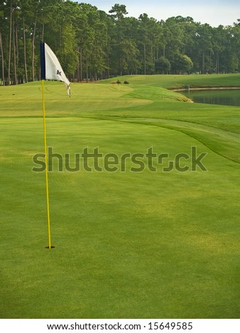 The flag and lots of beautiful green grass on this Myrtle Beach, South Carolina golf course. - stock photo
