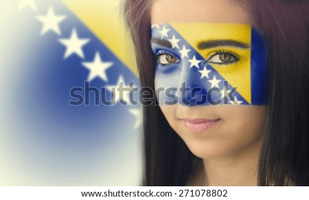 The flag of Bosnia and Herzegovina on the face of a smiling woman. / Color effects and custom white balance is added to this photo. - stock photo