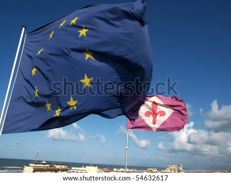 the flag of Florence and the European Union against the background of the deep blue sky.