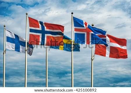 The flags of the countries of Scandinavia waving in the sky of a beautiful summer day. - stock photo