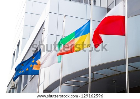 The Flags of the European Union, Poland, and other on office business building background - stock photo