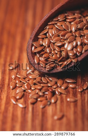 The flax seeds in a wooden bowl close up - stock photo