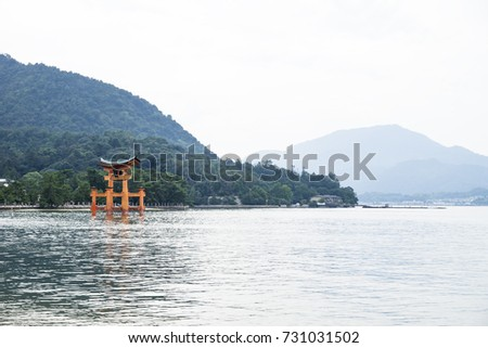 The Floating Torii gate in front of the mountains with trees in Miyajima, Japan.