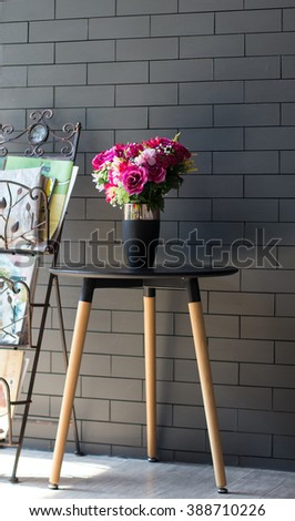 The flower vase on a  wooden table against a vintage wall, selected focus, narrow depth of field - stock photo