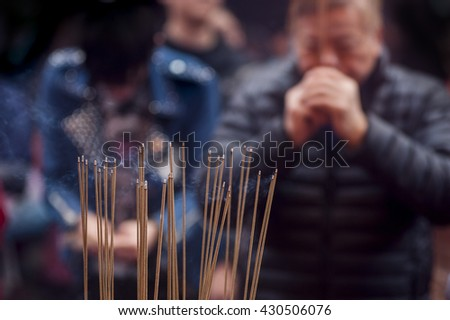 The focus of a soft, fuzzy-People lit incense sticks to pray in the temple during the first day of the Chinese new year, which is a traditional Chinese practice - stock photo