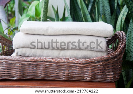 The folded towels on the basket near the swimming pool at the resort - stock photo