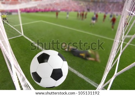 the foot ball in mesh of goal on background of stadium - stock photo