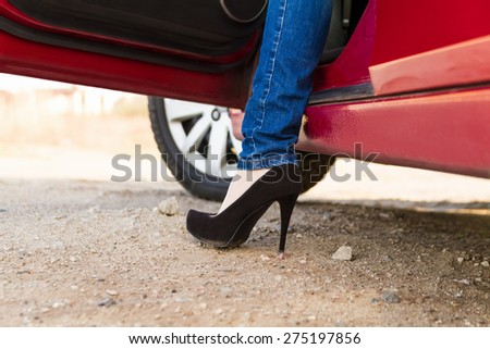 The foot of a beautiful woman from the open car door