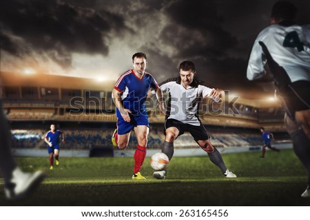 The football player kicks the ball in the game at the stadium - stock photo