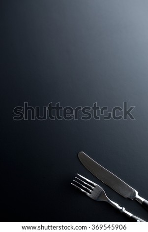 the fork and knife on black background - stock photo