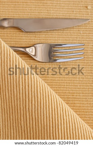 The fork, knife and yellow striped table cloth - stock photo