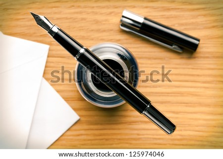 the fountain pen and inkwell on desk - stock photo
