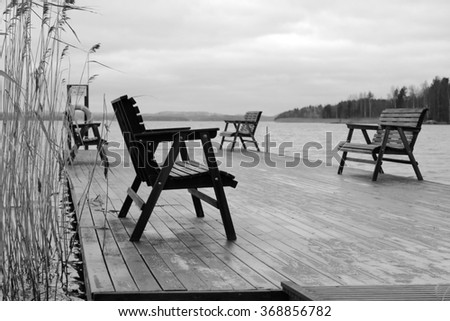 The four benches standing on the platform on the lake at the cold late autumn day in black and white colors with nobody around.