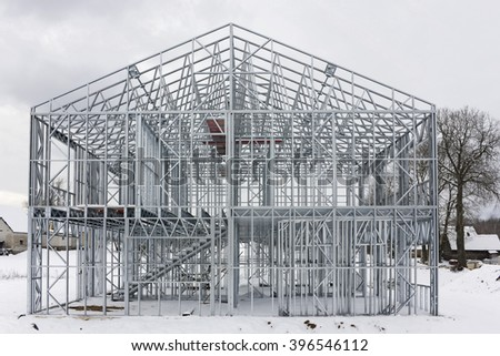 The framework of the modern rural house is made of galvanized metal beams and profiles. Front view.  Winter cloudy day landscape