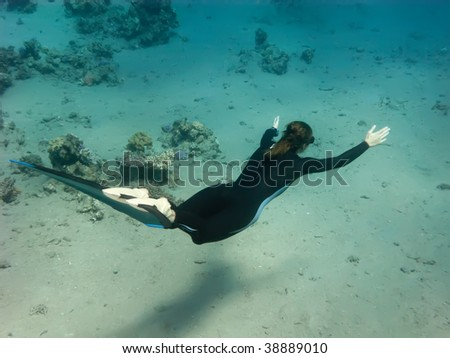 The freediver girl swims along sand Red sea bottom - stock photo