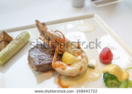 The french food, the fried prawns with shell in gravy and roast beef fillet with salad  - stock photo