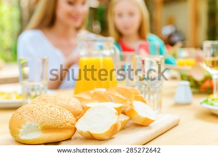 The freshest bread for dinner. Happy mother and daughter sitting at the dining table outdoors and enjoying meal while fresh bread laying on foreground  - stock photo