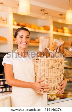 The freshest bread for our customers. Beautiful young woman in apron holding basket with bread and smiling while standing in bakery shop - stock photo