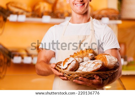 The freshest bread for you. Cropped image of young man in apron holding basket with baked goods and smiling while standing in bakery shop - stock photo