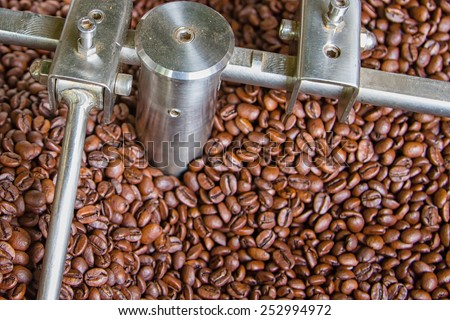 The freshly roasted coffee beans from a large coffee roaster being poured into the cooling cylinder - stock photo