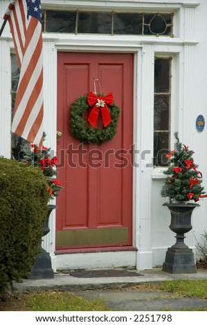 The front door of an early New England house with a wreath hanging on a red door and american flag on side