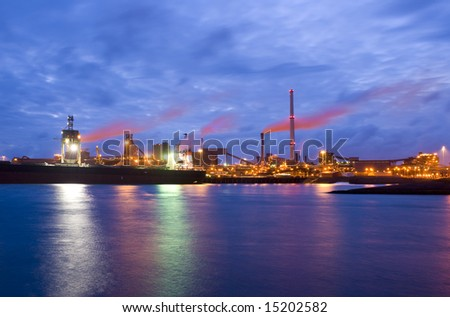 The front-end of a steel plant, with a bulk carrier with iron ore being unloaded - stock photo