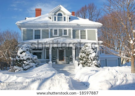 The front of a large older home covered in deep snow. - stock photo