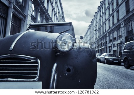 The front of an old run-down car (Citroen 2CV) in a little street in Paris, France.