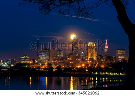 The full moon of November rises over Cleveland Ohio with reflections in Lake Erie - stock photo