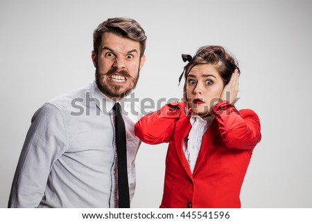 The funny business man and woman communicating on a gray background. Business concept of relationship of colleagues